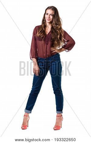 Full length portrait of coquettish female in jeans isolated on white background