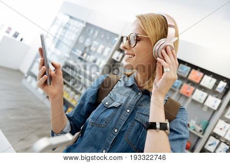 Happy young woman trying out the latest model of headphones after plugging them into her phone at a department store.