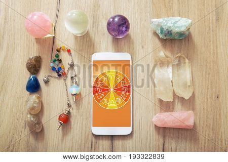 Zodiac signs and smart phone in hand. Concept of modern astrology.