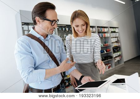 Cheerful couple having a chat over a template digital tablet while standing at a store display and shopping for new technological devices.
