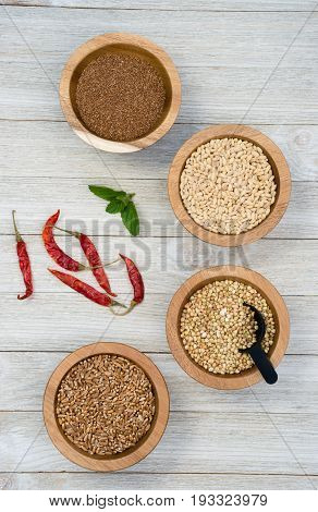 Wheat Berries Buckwheat Groats Pearl Barley Farrow in Bowls with Red Peppers on the side