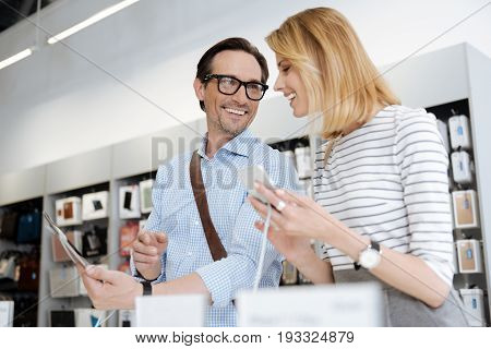Female and male shoppers beaming while having a chat over the newest gadgets while standing at a display of a local department store.