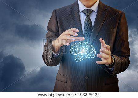 Businessman Showing Brain Against The Sky.