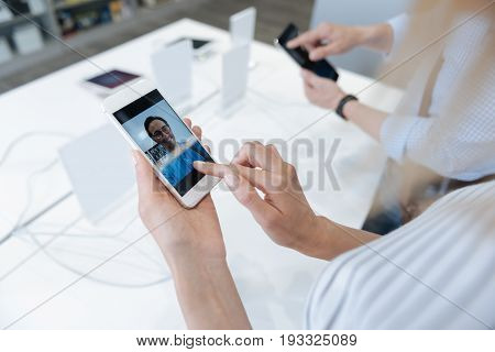 Scaled up shot of shoppers standing at a store display and making video calls while testing technological capabilities of mockup cellphones.