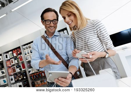 Smiling man and woman wearing casual attire standing at a store display and trying out technological devices during their shopping outing.