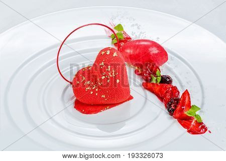 Heart shaped sweet dessert with berries served on the white plate