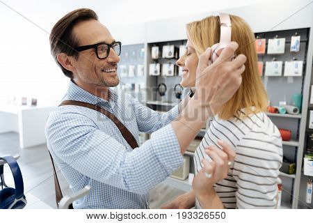 Full of life smiling couple wearing casual attire trying out the latest model of headphones while standing at a display and shopping for new devices.