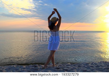 girl in a straw hat at sunset on the seashore