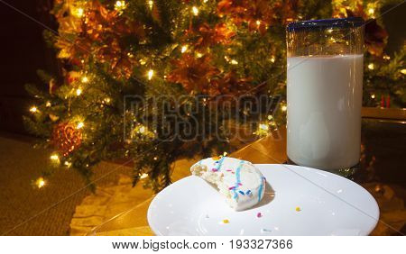 Cookie that is half eaten with milk near a lit Christmas tree