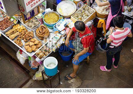 CHIANG MAI THAILAND - AUGUST 24: Man sells food at the market on August 24 2016 in Chiang Mai Thailand.