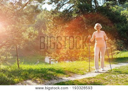 Sport activities. Positive joyful aged woman holding walking poles and practicing Nordic walking while leading healthy lifestyle