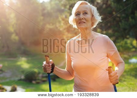 Healthy activity. Delighted positive senior woman holding walking poles and smiling while practicing Nordic walking