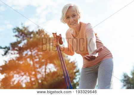 Come here. Joyful senior nice woman holding walking poles and smiling while stretching out her hand to you
