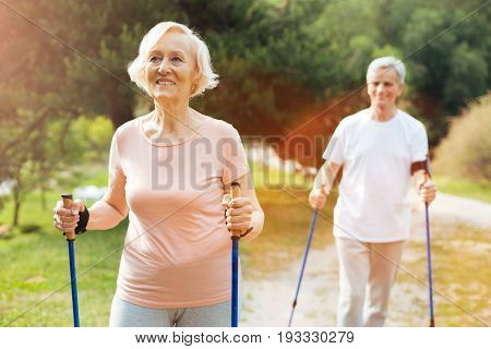 Elderly couple. Happy positive elderly woman smiling and holding Nordic walking poles while hiking with her husband