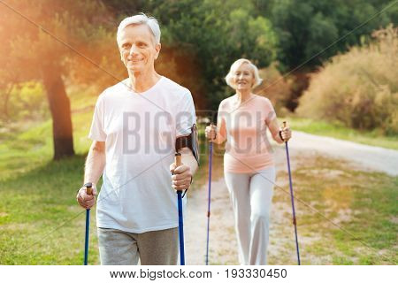 Positive mood. Handsome cheerful elderly man holding Nordic walking poles and smiling while being in a positive mood
