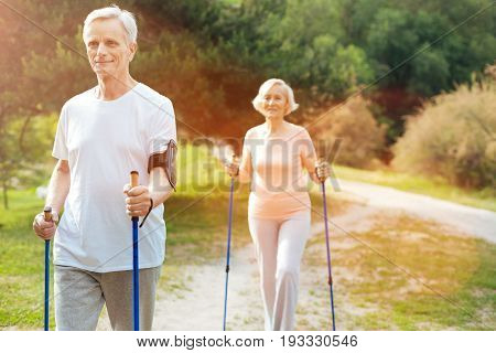 Sports activity. Handsome happy nice man holding walking poles and practicing Nordic walking while being outdoors