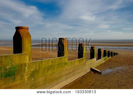 Wooden wave breaker on camber Sands beach at low tide, East Sussex England