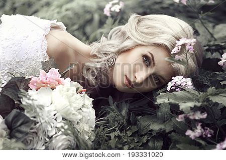 Portrait of a beautiful young woman as a princess. Lies in the forest with flowers.