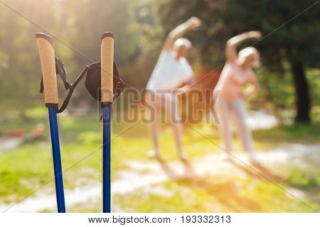 Professional equipment. Selective focus of professional walking poles with pleasant active elderly people exercising in the background