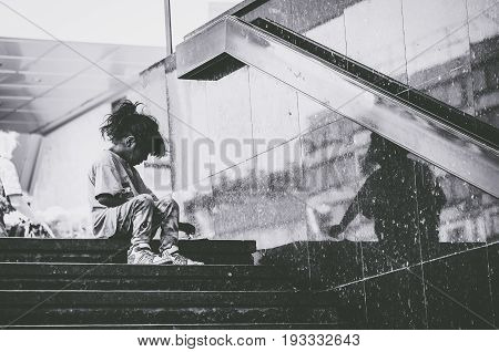 Homeless. Homeless child eating on the stairway in the street. Social documentary street. September - 16. 2016. Novi Sad, Serbia. Editorial image. Dark black and white.