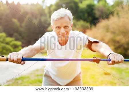 Being in use. Selective focus of a professional walking pole being in hands of a delighted positive elderly man while exercising