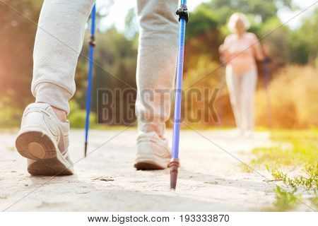 Race walking. Close up of walking poles being used by a nice sporty active man while doing race walking
