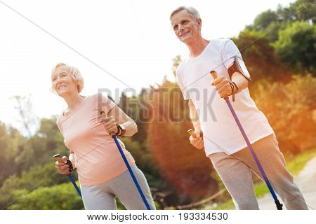 Walking activity. Joyful active aged couple holding walking poles and walking along the route while being in the park