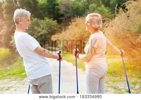 Delighted couple. Happy positive elderly people holding walking poles and looking at each other while having fun together