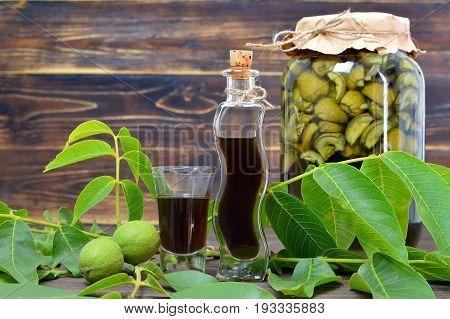 Preparing green walnut liqueur on wooden background