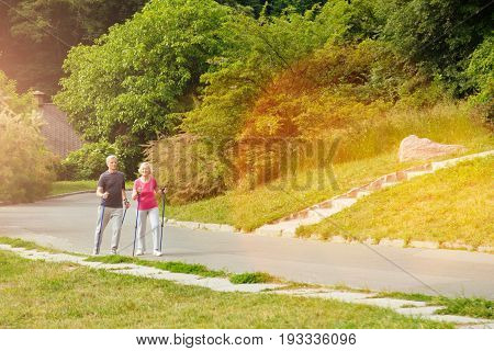 Favourite activity. Active nice elderly couple holding walking poles and walking along the road while taking pleasure in the activity