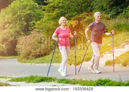 We love sport. Delighted positive aged couple walking along the road with the walking poles and smiling while leading an active lifestyle