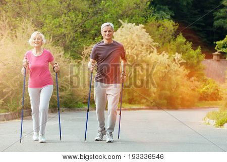 Time for sport. Happy nice aged couple using walking poles and taking steps forward while walking in the countryside