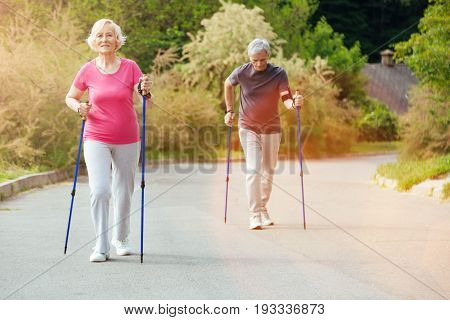 Active lifestyle. Joyful nice senior couple holding poles and walking with them along the park while keeping fit