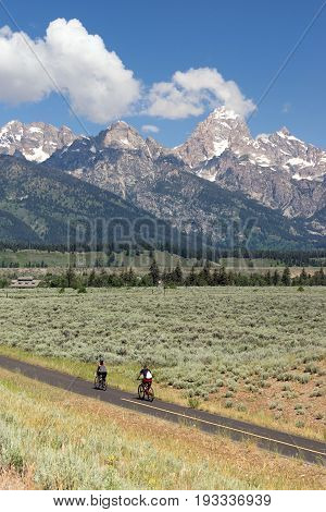 Two people ride along in the forground Rocky Mountains in the background