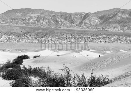 A hiker moves in the sand dunes of Death Valley National Park