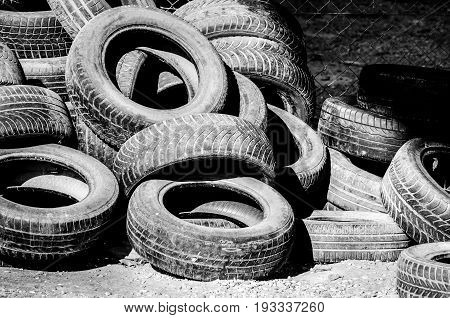 Car tires. Old used car tires on the junk yard. Black and white. Hard contrast.