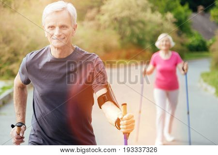 Healthy way of life. Delighted joyful nice man holding walking poles and practicing sport while being in the park