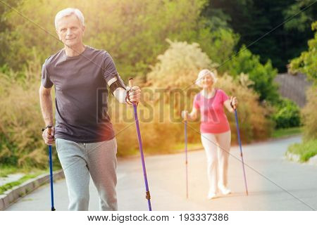 I love sport. Happy positive elderly man practicing Nordic walking with his wife and smiling while enjoying this sports activity