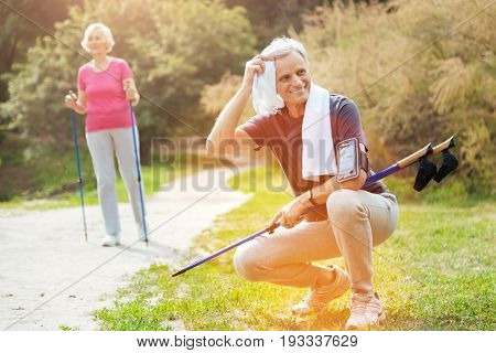 Intensive outdoor training. Positive delighted nice man holding walking poles and using the towel while wiping his sweat away
