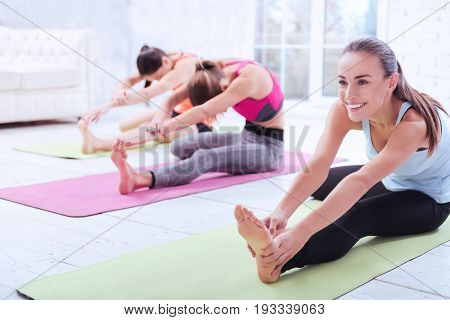 Warming up. Young smiling pretty woman is leaning forward to her foot while doing some stretching with friends at gym.