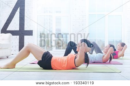 Working hard. Side view of pretty youthful women lying on carry mates and doing abdominal crunches at gym.