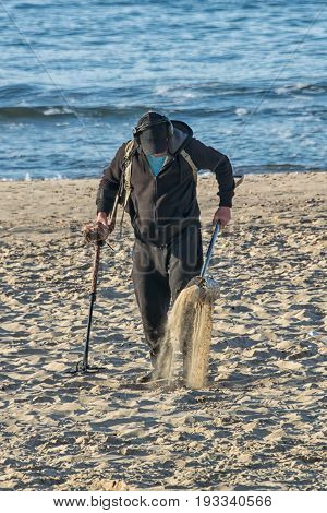 A metal detector searching in the sand on a beach with the sea in the background in upright vertical format