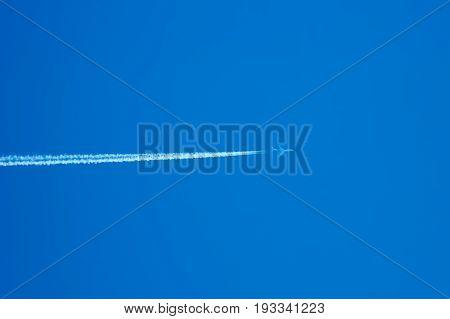 Passenger jet flying high in clear blue sky leaving long white trail