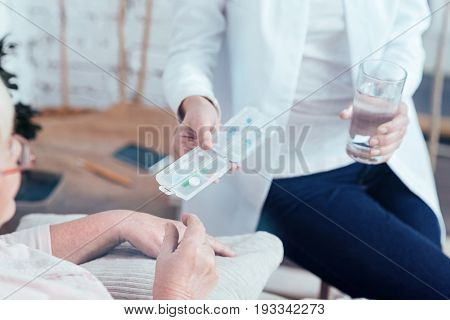 Helping needy aged people . Friendly proficient medical doctor sitting in the bedroom and helping pensioner while offering pills and glass of water
