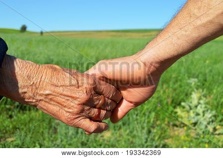 Unity and solidarity, to be together in the face of difficulties, the son is holding the hand of his elderly mother,