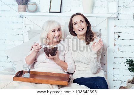 Enjoying life with my grandmother. Thoughtful glad young woman sitting at home and taking care of old grandmother while pensioner enjoying breakfast