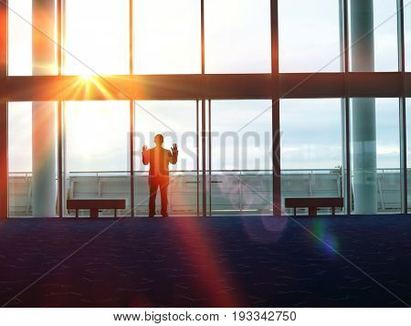 Rear view of a silhouette businessman looking out window at the airport lobby