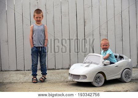 Two сute little dude plays with a toy car on a rural farmstead in a hot summer