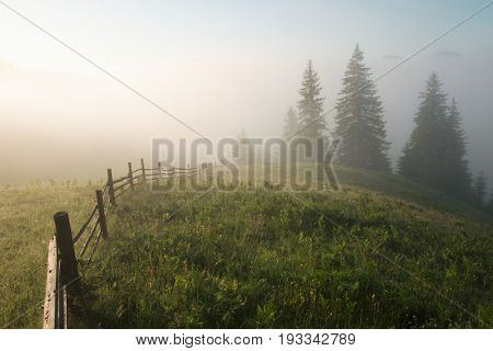 Mountain valley during sunrise. Woden fence on foggy meadow. Located place: Carpathians, Ukraine, Europe