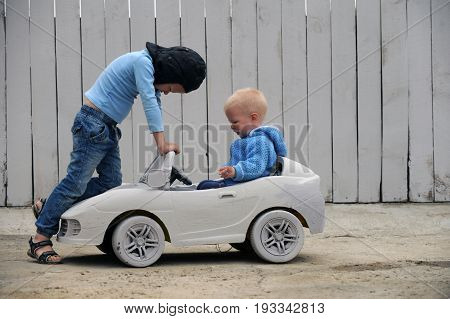 Two Cute boy plays with a toy car and a race prize for a rural farmstead in a hot summer